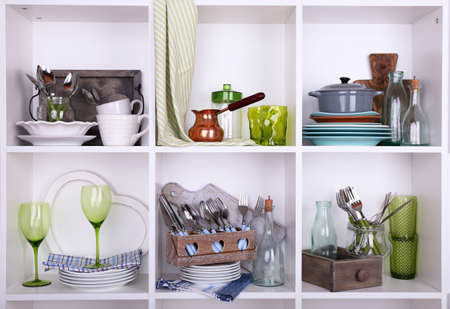 Kitchen utensils and tableware on beautiful white shelves Stock Photo