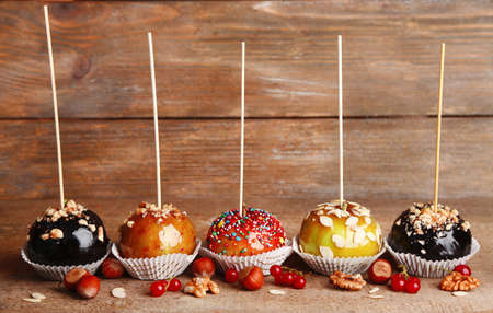 gritting: Sweet caramel apples on sticks with berries, on wooden table