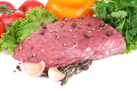 Raw beef meat with vegetables and spices isolated on white photo