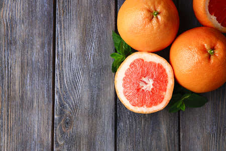 Ripe grapefruits on wooden background Imagens