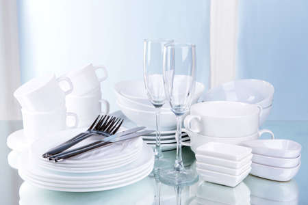 Set of white dishes on table on light background Фото со стока