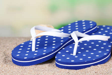 Color flip-flops on sand, on nature background photo