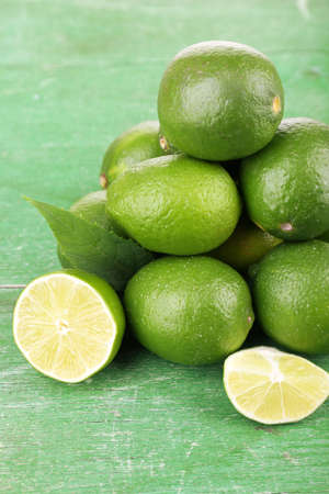 Fresh juicy limes on old wooden table photo