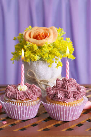 Tasty cupcakes on table, on fabric background photo