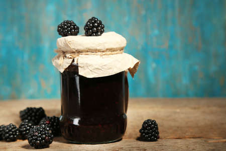 Tasty blackberry jam and fresh berries, on wooden background photo