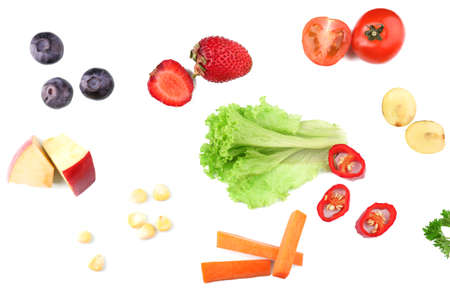 Different slices of vegetables and berries on wooden table Stock Photo