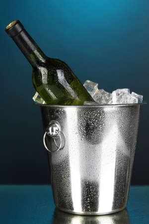 Bottle of wine in ice bucket on dark blue background photo