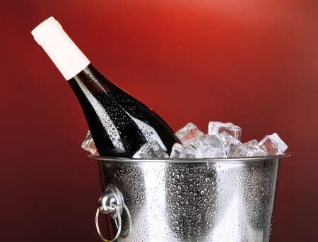 darck: Bottle of wine in ice bucket on darck red background Stock Photo
