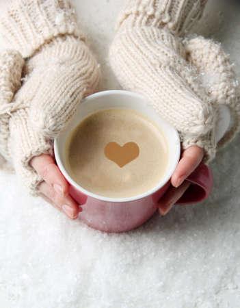 明るい背景上の温かい飲み物と女性の手