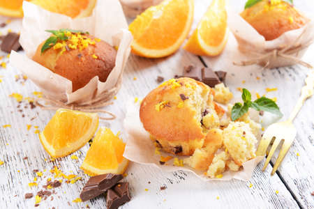 Tasty cupcakes with orange on table close-up photo