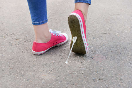 the sole of the shoe: Foot stuck into chewing gum on street Stock Photo