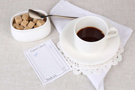 Check and cup of coffee on table close-up photo