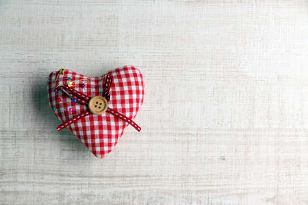 Fabric heart with color  pins on wooden background photo