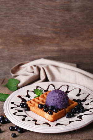 Tasty belgian waffles with ice cream on wooden table photo