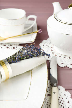 Dining table setting with lavender flowers on wooden table background photo