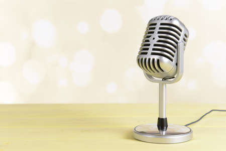 Vintage microphone on table on light yellow background Stock Photo
