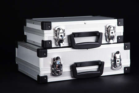 Silvery suitcases on black background photo