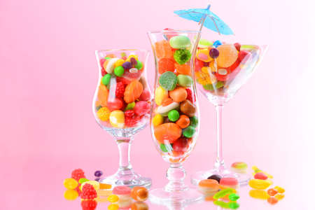 Different colorful fruit candy in glasses on pink background Stock Photo