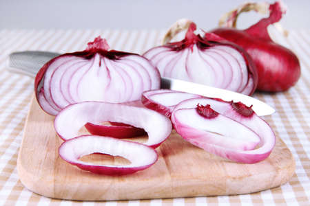 aftertaste: Fresh red onions on cutting board close up