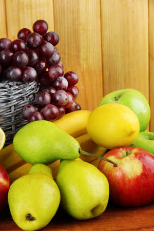 Composition of different fruits with basket on table on wooden background photo