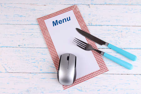 Computer mouse with menu and cutlery on wooden background photo
