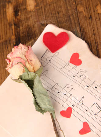 Red paper hearts, dried rose on music book, close-up, on wooden background photo
