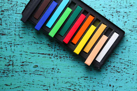 white chalks: Colorful chalk pastels in box on color wooden background