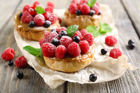 Sweet cakes with berries on table close-up photo