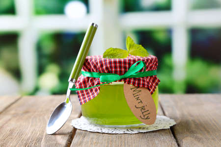 Homemade mint jelly in glass jar, on wooden table, on bright background photo
