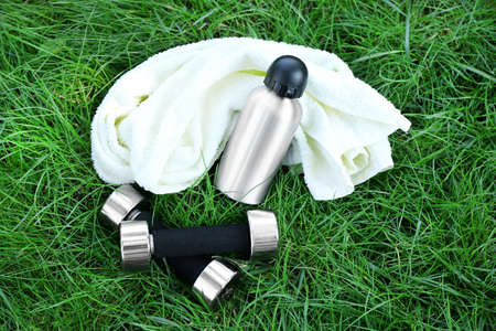Dumbbells and bottle with water, towel on green grass background Stock Photo