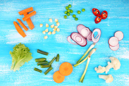 Different kind of raw vegetables on wooden table photo