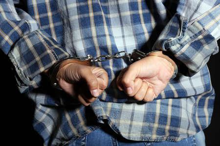 Criminal hands locked in handcuffs on dark background photo