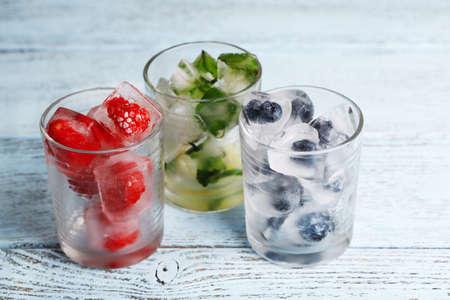 cubo: Cubos de hielo con hojas de menta, frambuesa y arándanos en copas, sobre el color de fondo de madera