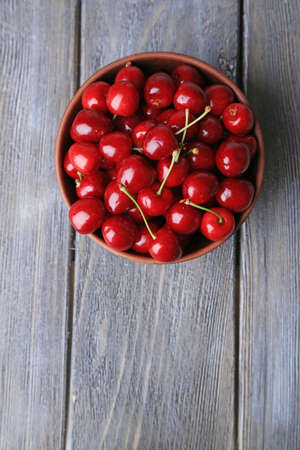 Sweet cherries in color bowl on wooden background