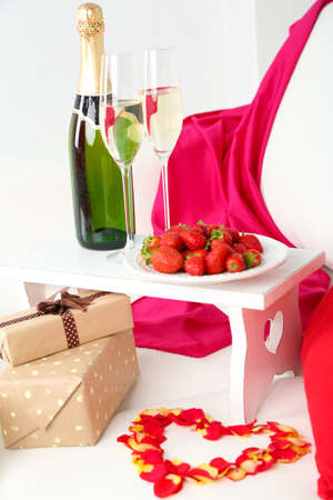Romantic still life with champagne, strawberry and roses on sofa photo