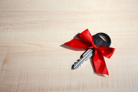Car key with colorful bow on wooden background photo