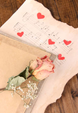 Red paper hearts on music book, close-up, on wooden background photo