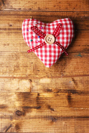 pinhead: Fabric heart with color  pins on wooden background Stock Photo