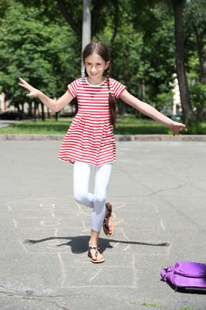 Cute girl playing hopscotch outside photo