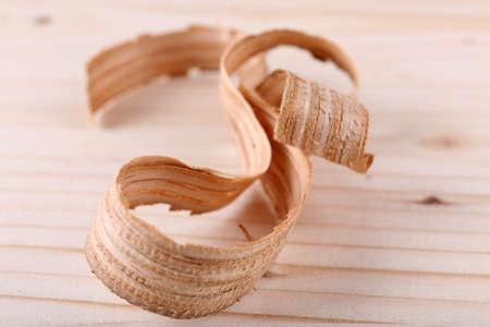 filings: Wood shavings on wooden background closeup
