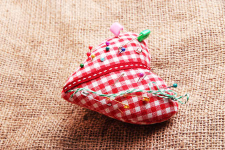 Fabric heart with color pins on sackcloth background photo