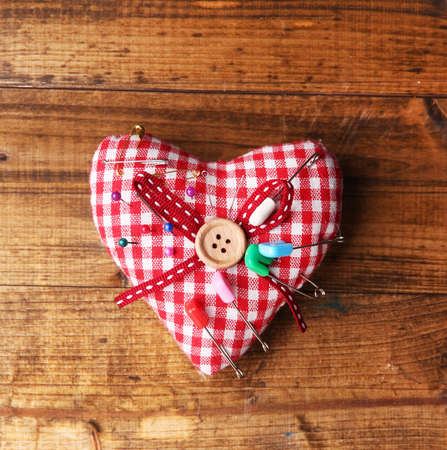 Fabric heart with color pins and safety pins on wooden background photo