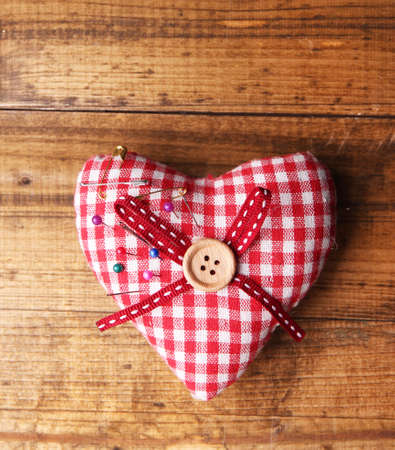 Fabric heart with color  pins on wooden background Stock Photo