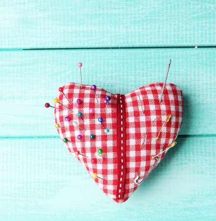 pinhead: Fabric heart with color and safety pins on wooden background