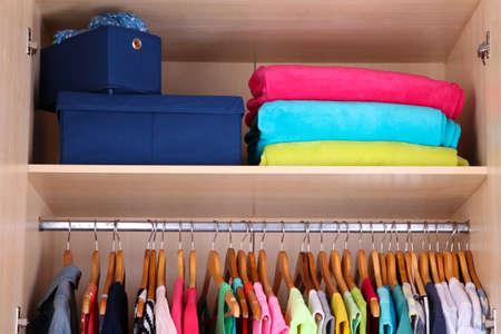 vestidos: Ropa de colores colgando en el armario