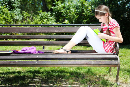 Cute girl drawing on bench in park photo