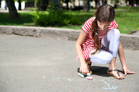 Cute girl drawing with chalk on asphalt photo