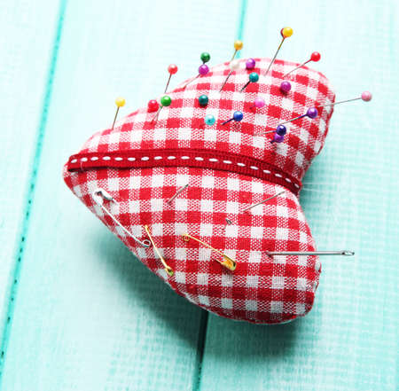 Fabric heart with color and safety pins on wooden background photo
