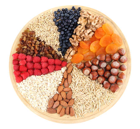 sectors: Big round plate with raisins, raspberries, oatmeal, nuts and dried apricots divided on sectors on white background isolated