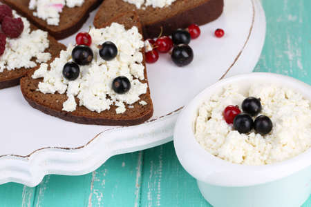 Bread with cottage cheese and berries on wooden tray close-up photo